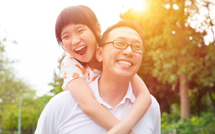 Man and daughter smiling outside